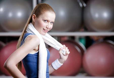 Portrait of a young sportive girl in tracksuit with white towel against a great variety of colorful balls Stock Photo - 17457729