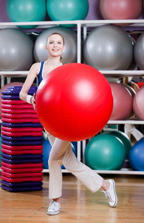 Woman in sports wear exercises with red gym ball Stock Photo - 17457741