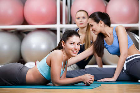 Group of sportswomen have a rest in the gym centre against set of colorful balls Stock Photo - 17457738