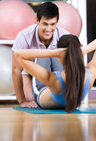 situp: Athletic woman does situps with coach in training gym Stock Photo