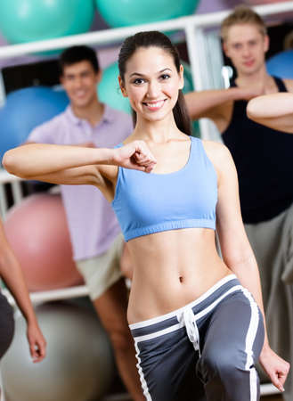 keep fit: Sexy female coach exercises with her group at the gym in a fitness class helping them to loose weight Stock Photo