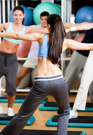 Sexy coach exercises with her group at the gym in a body shaping class photo