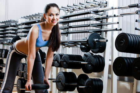Strong woman chooses appropriate dumbbells in sport centre photo
