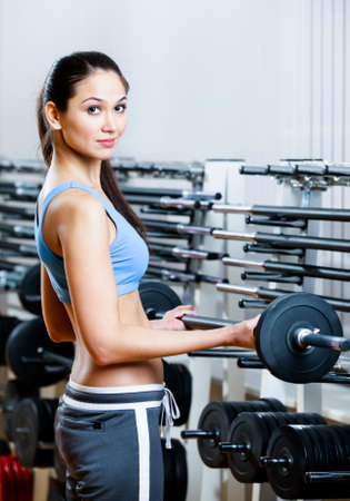 keep fit: Woman lifts dumbbells in sport centre to develop muscles