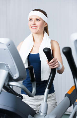 Young athlete woman training on gym equipment in gym photo