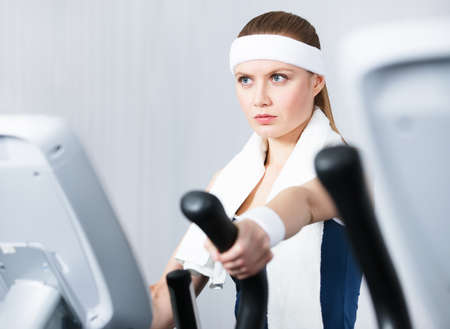 Young woman training on training apparatus in gym photo