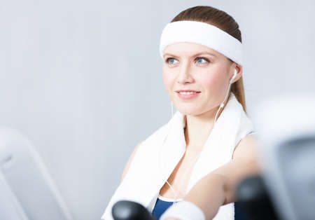 Young sportswoman training on gym equipment in gym Stock Photo - 17457706