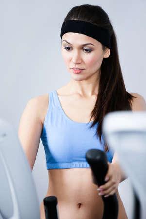 cintillos: Mujer joven formación deportiva en aparatos de entrenamiento en el gimnasio Foto de archivo