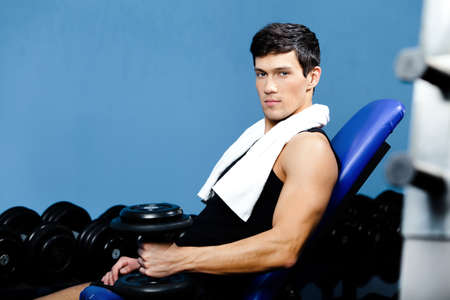 Sporty man in sportswear rests holding a weight in the hand against a set of dumbbells photo
