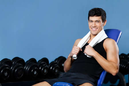 Athletic man rests sitting on blue simulator in gym Stock Photo - 17457775