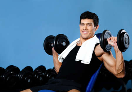 Smiley bodybuilder exercises with weights in fitness gym against a set of dumbbells photo