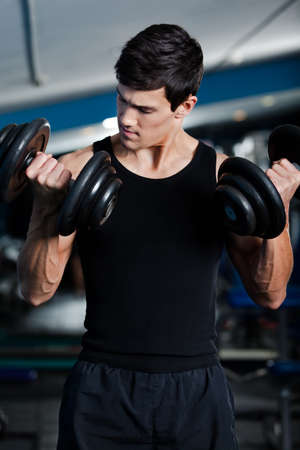 Handsome muscular man uses his dumbbells to exercise flexing bicep muscle  Stock Photo - 17457889