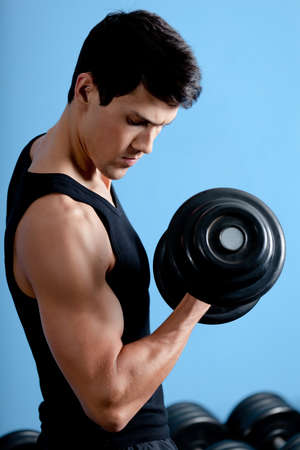 Handsome muscular athletic man uses his dumbbell to exercise flexing bicep muscle photo