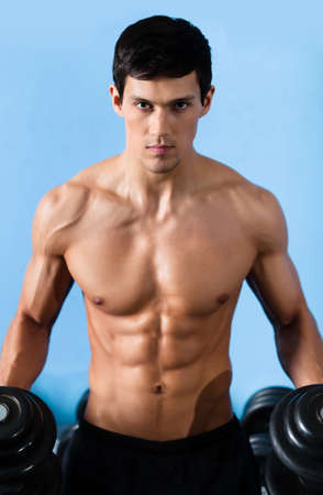 naked male body: Handsome muscular man with sexy body uses his dumbbell to exercise flexing bicep muscle Stock Photo