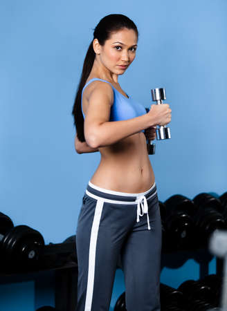 Sportive woman works out with dumbbells in fitness gym Stock Photo - 17457722