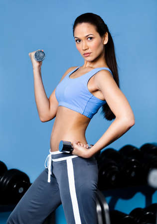 Athletic woman works out with dumbbells in training gym photo