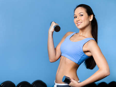 Sportswoman works out with dumbbells in gym photo