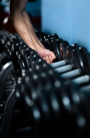 body building: Hand of a man choosing a dumbbell out of set of black weights