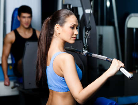 Athletic young woman works out on training apparatus in gym class Stock Photo - 17457806