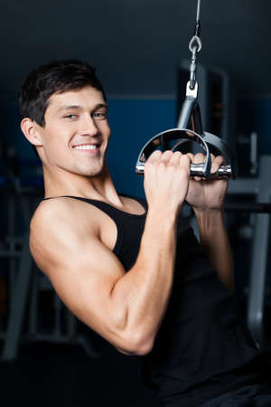 Athletic young man works out on gym equipment in fitness gym Stock Photo - 17457779