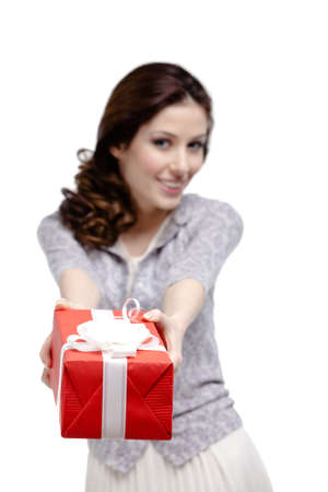 Young woman makes a gift wrapped in red paper, isolated on white photo