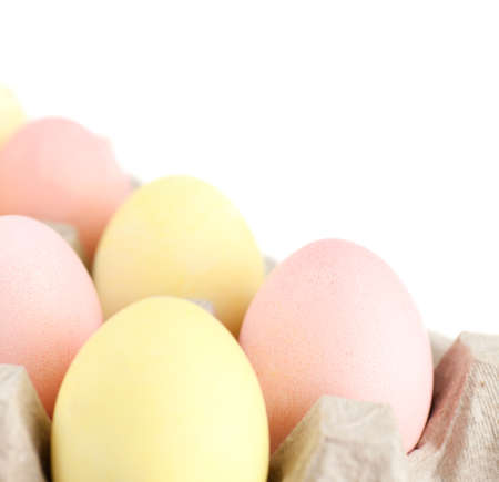 chucky: Multicolored eggs are in the cardboard box for egg delivering, isolated on white
