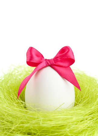 chucky: Egg with pink bow is in the nest of sisal fibre, isolated on white Stock Photo