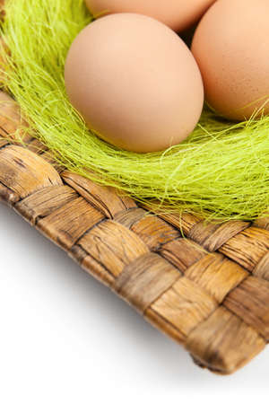 chucky: Brown easter eggs are on wattled square plate with sisal green fibre, isolated on white