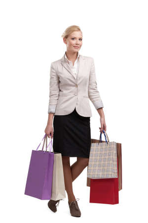 Attractive attractive business woman in a light beige suit holding shopping bags, isolated on white background photo