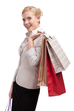 Attractive blonde businesswoman in a light beige suit holding shopping bags, isolated on white background photo