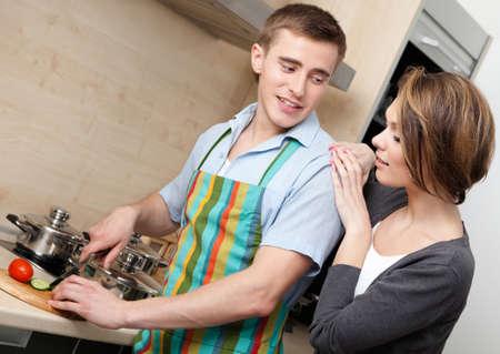 gladly: Hombre en chuletas delantal verduras para la cena para su novia en la c�moda cocina moderna