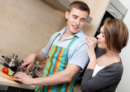 short cut: Man in apron chops vegetables for dinner for his girlfriend in the modern comfortable kitchen
