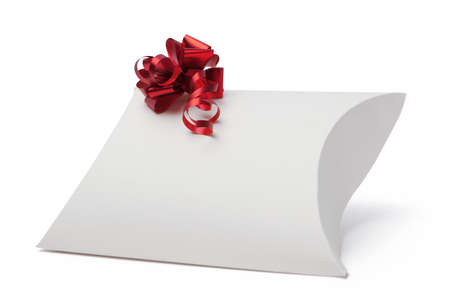 White gift box with red ribbon, isolated on white. Symbol of feast and happy holiday photo