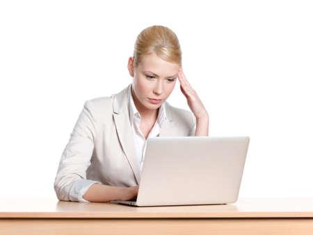 cansancio: Joven empresaria cansado sentado en un escritorio con ordenador portátil, aislado