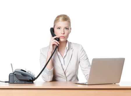 seriously: Young businesswoman sitting at a office table and holding phone handset, isolated