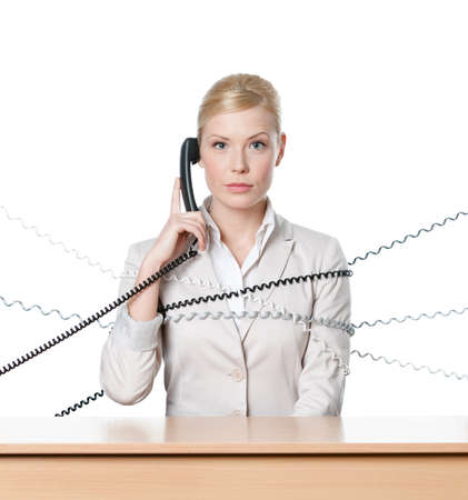 Young businesswoman sitting at a office desk tied with phone cord, isolated photo