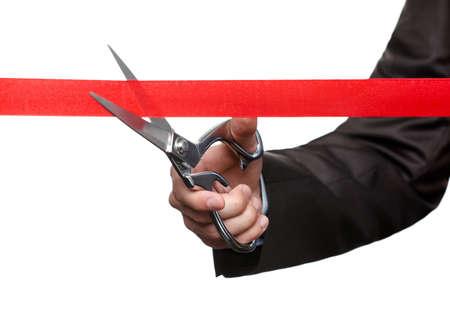 taglio del nastro: Un uomo d'affari di taglio di un nastro scarlatto con le forbici, isolato su bianco