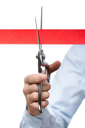 A businessman cutting a red ribbon with scissors, isolated on white photo