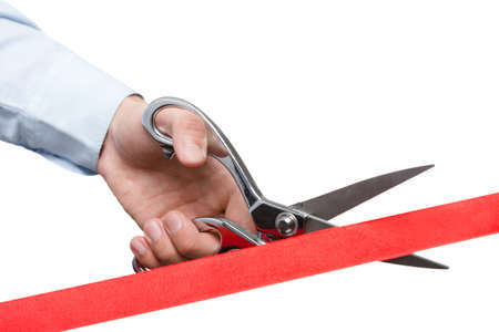 A man cutting a ribbon with scissors, isolated on white photo