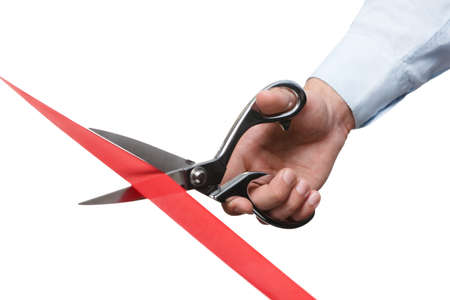 A business man cutting a ribbon with scissors, isolated on white photo