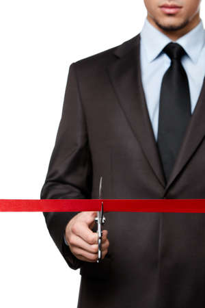 A business man cutting a red ribbon with scissors, isolated on white photo