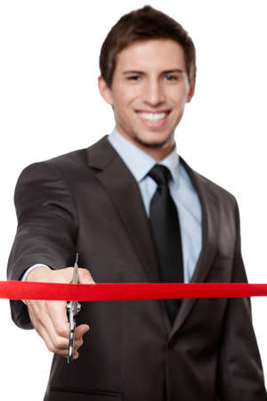 A business man cutting a scarlet satin ribbon with scissors, isolated on white photo
