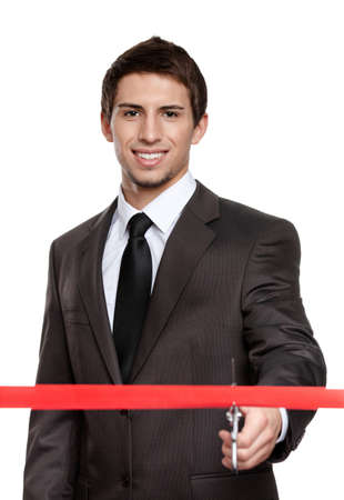 A man in a business suit cutting a red silk ribbon with scissors, grand opening or beginning concept, isolated on white photo