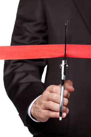 new start: A businessman cutting a ribbon with scissors, isolated on white