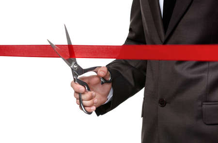 A man cutting a red satin ribbon with scissors, isolated on white photo