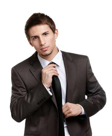 hair tie: Man straightens his black tie, isolated on white Stock Photo
