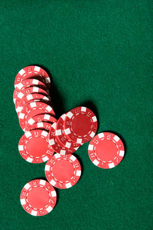 Heap of red poker chips on the green table. Symbol of risky entertainment photo