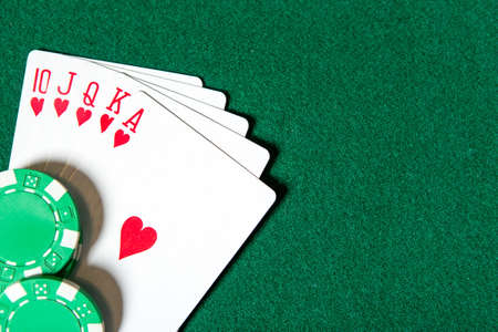 Royal Flush poker card sequence near chips on a green table. Challenge to the casino photo
