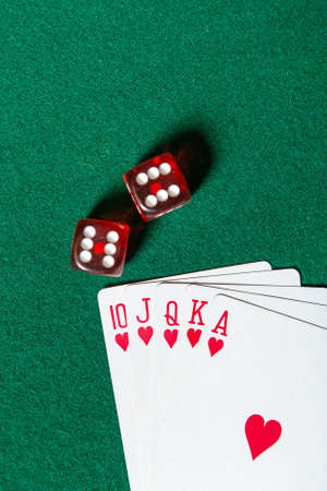 Royal Flush poker card sequence near dices on a green table. Risky entertainment of gambling photo