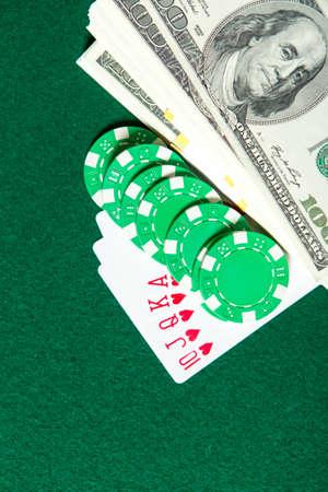 kockázatos: Royal Flush Póker kártya sorozatot, zöld chipek és pénzt egy zöld asztal. Kockázatos szórakoztató szerencsejáték Stock fotó